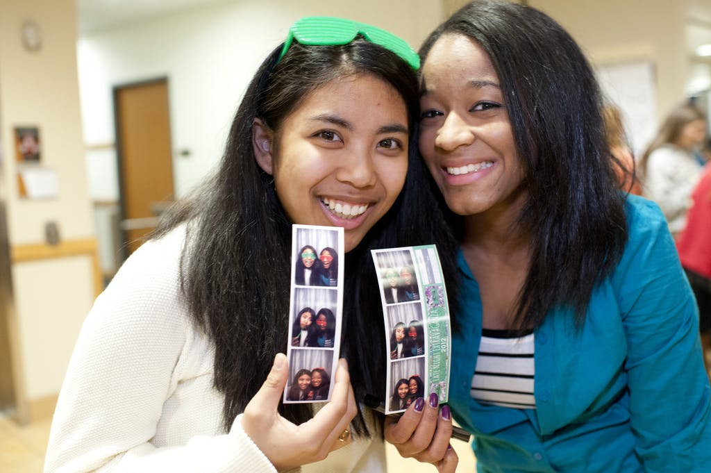 Two students holding pictures from a photo booth