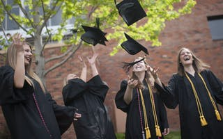 Undergrad students in graduation gowns toss their caps.