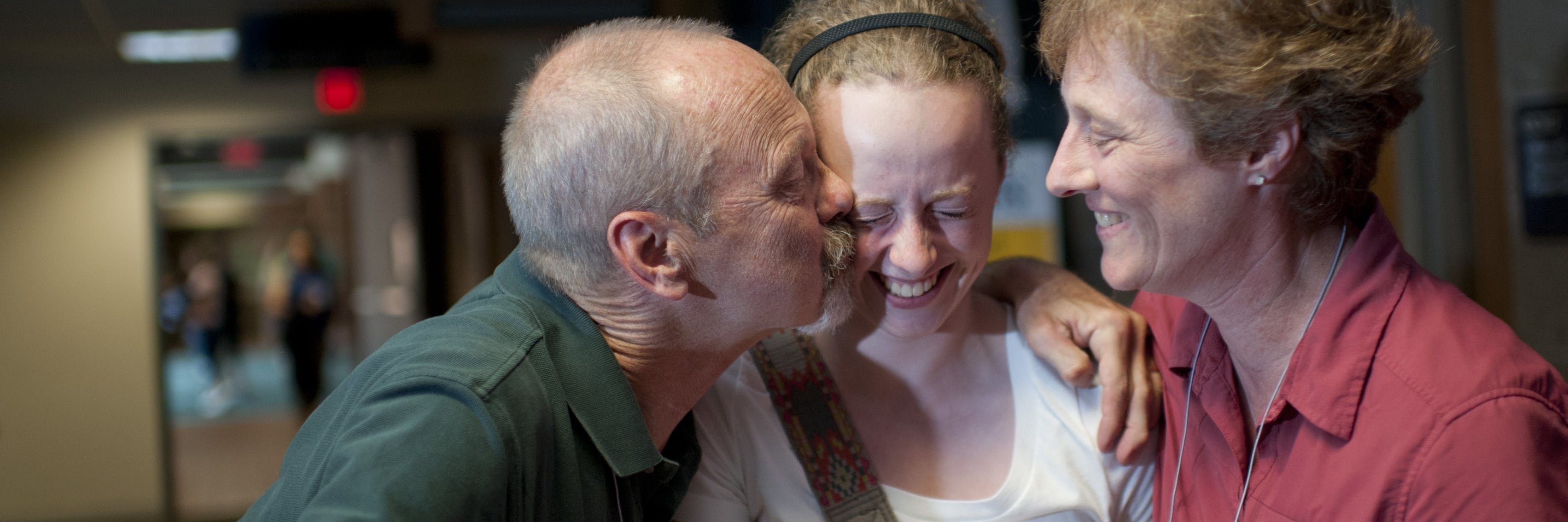 A dad kissing his daughter