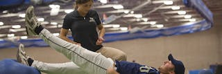 Athletic training leadership student stretches baseball player