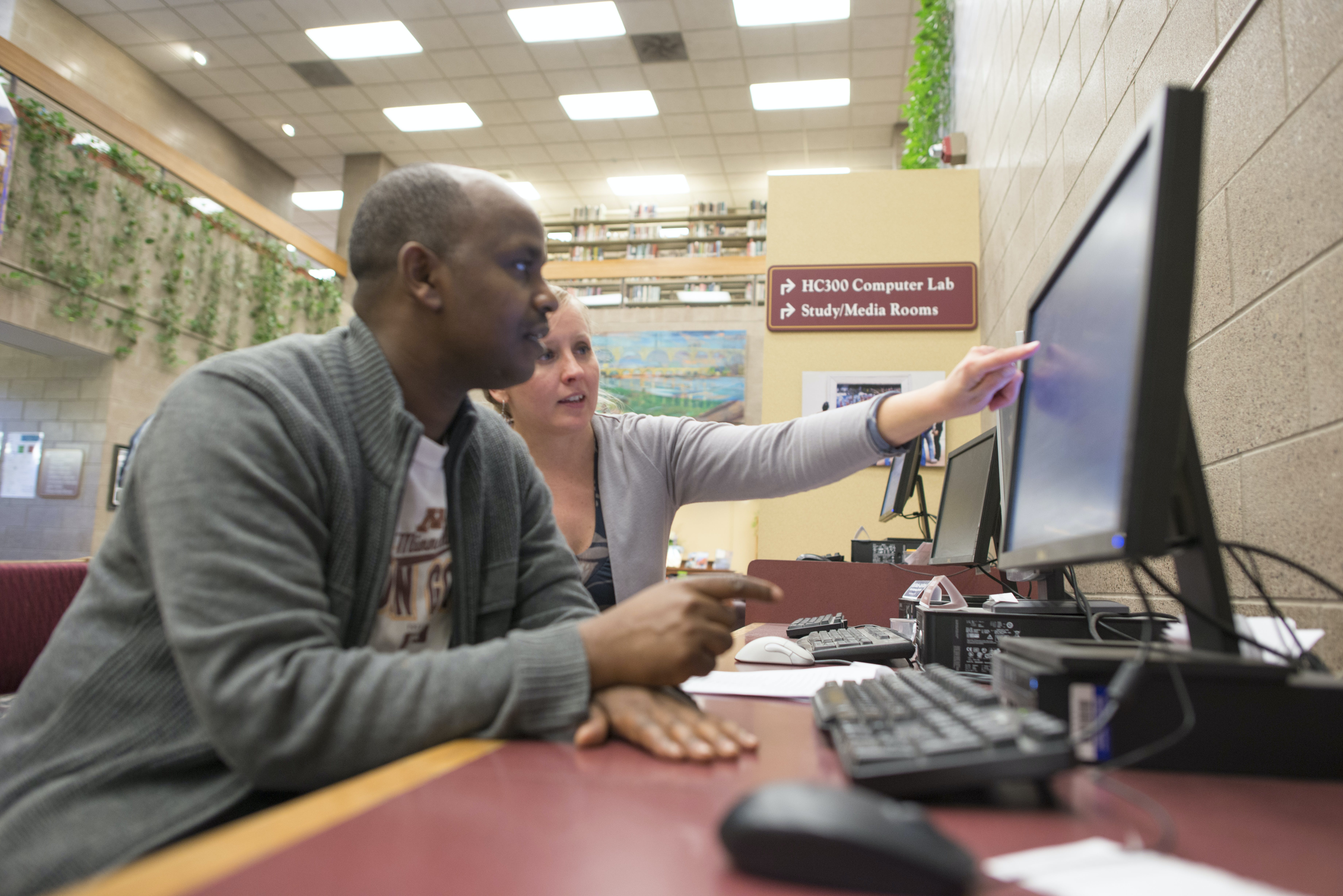 Library staff helps faculty on computer