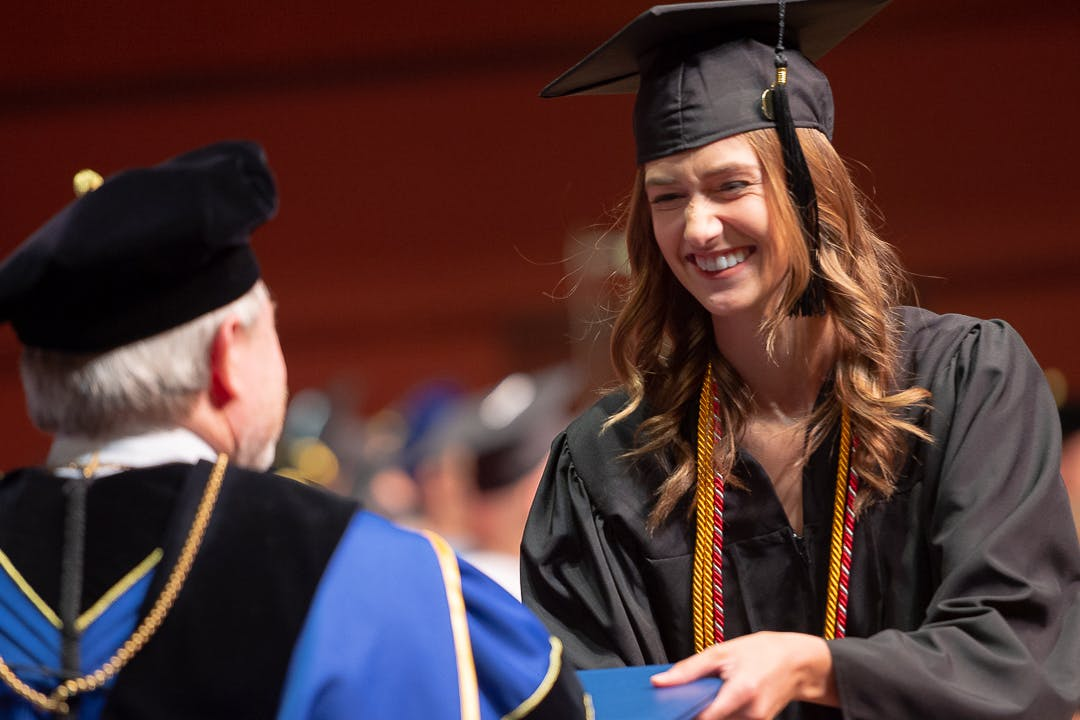 A student receives her diploma from President Jay Barnes at Spring Commencement at Bethel University