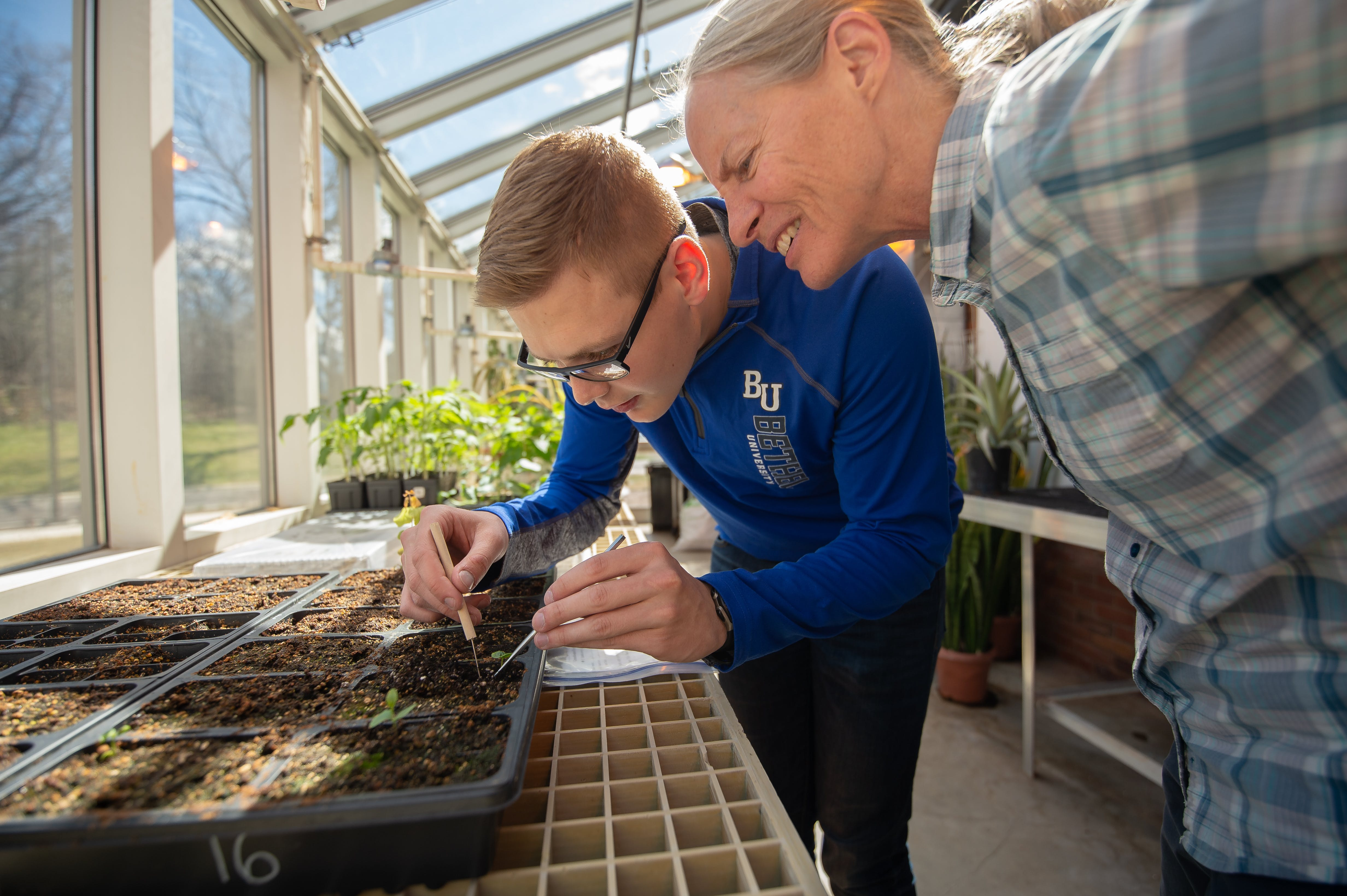 Student Joshua Turek and Associate Professor of Biology Amy Dykstra work together in Bethel's greenhouse
