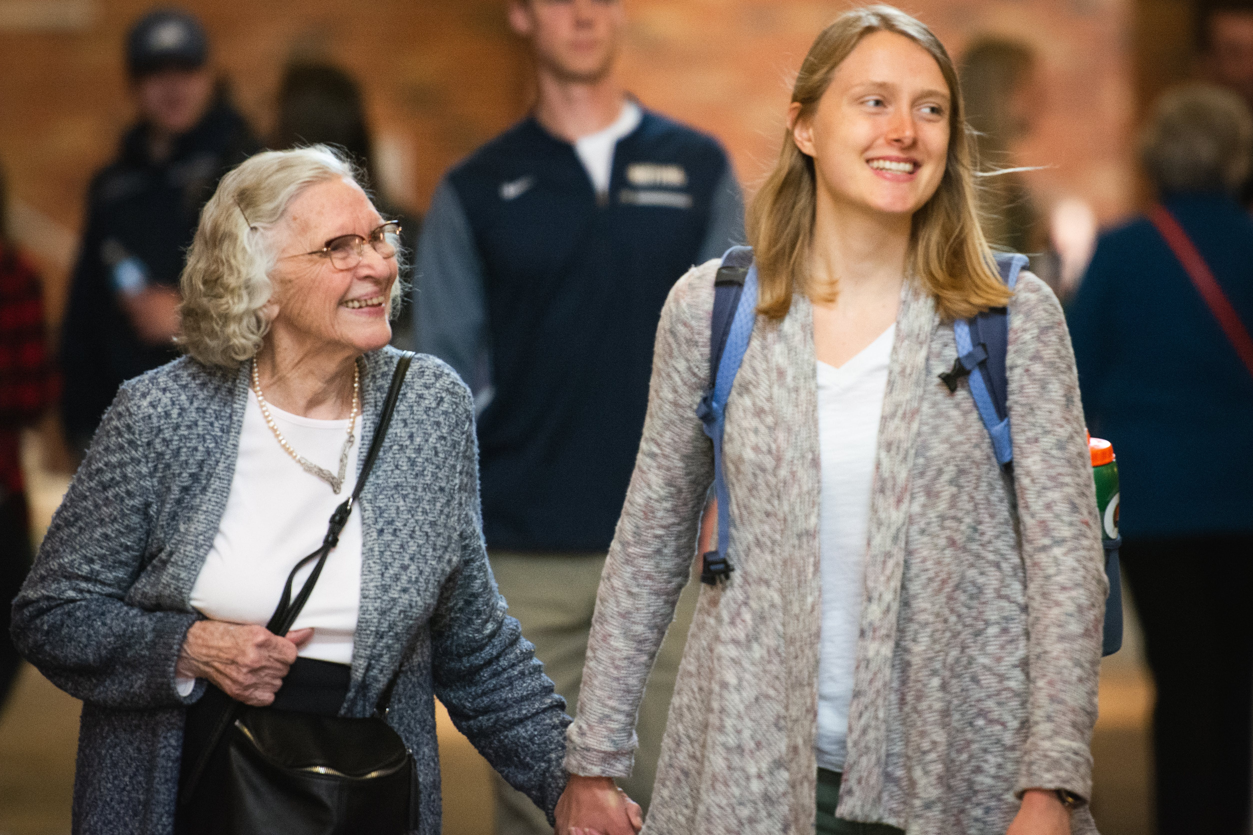 Student and grandparent hold hands in the hallway.