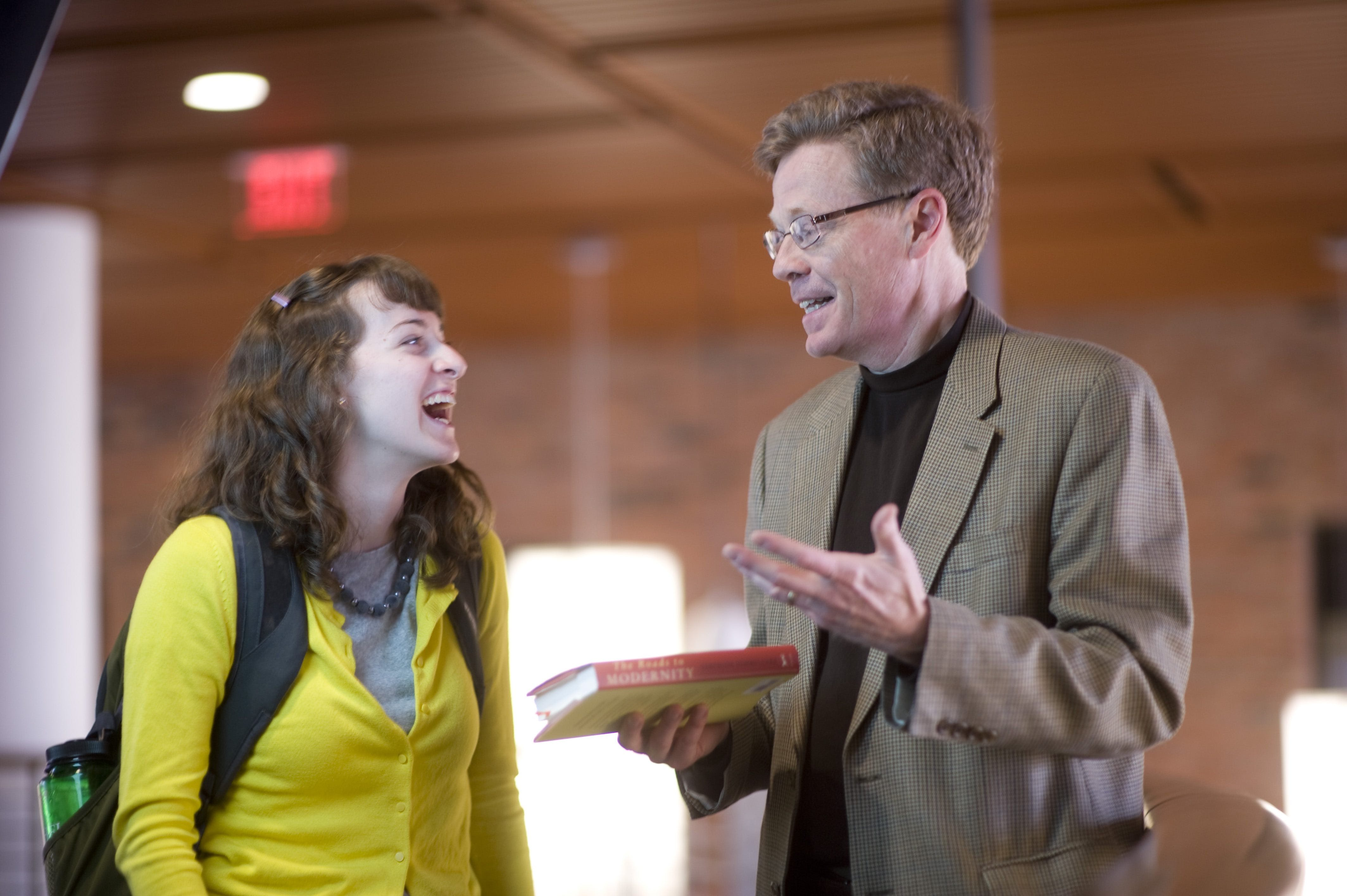 A Bethel student interacts with a professor between classes.