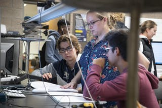 Students and a professor do research in a physics lab at Bethel University.