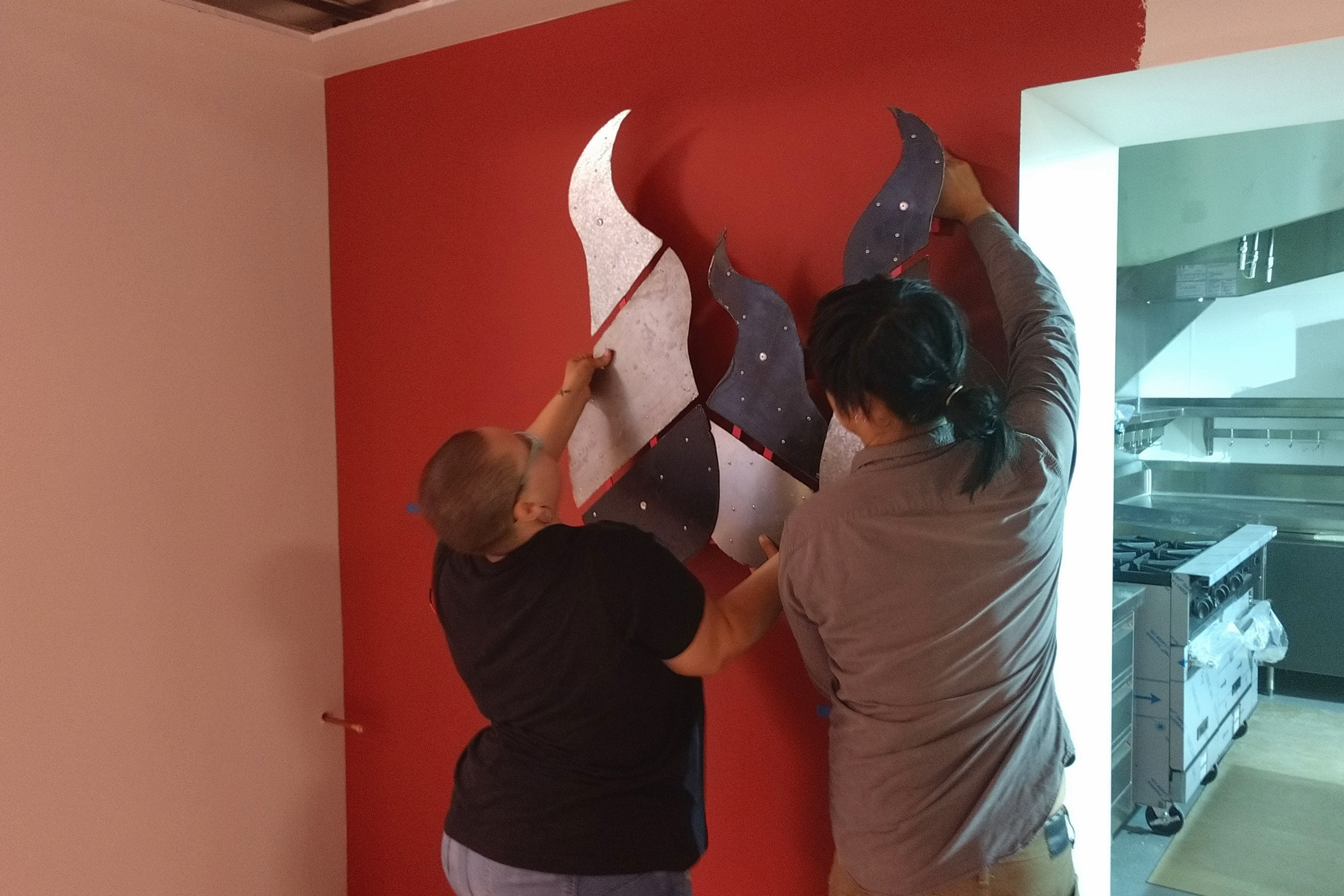 The student artist helps install the artwork at St. Matthew's
