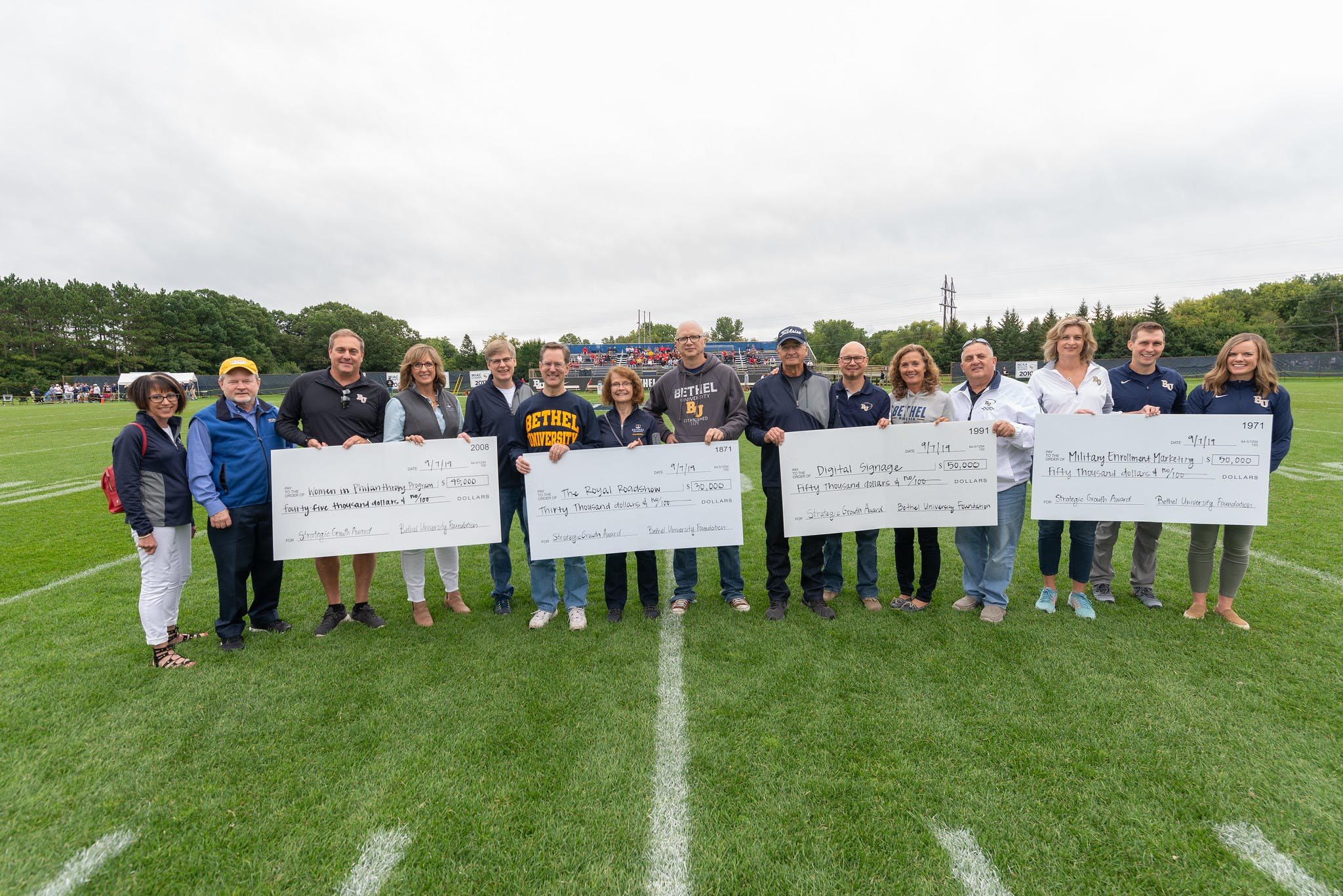 Proponents of the four winning proposals received checks for their groups before the September 7 football game.