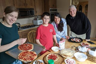 Abigail Gundy '15 (left) makes pizza with her brother Josiah and their parents during quarantine.
