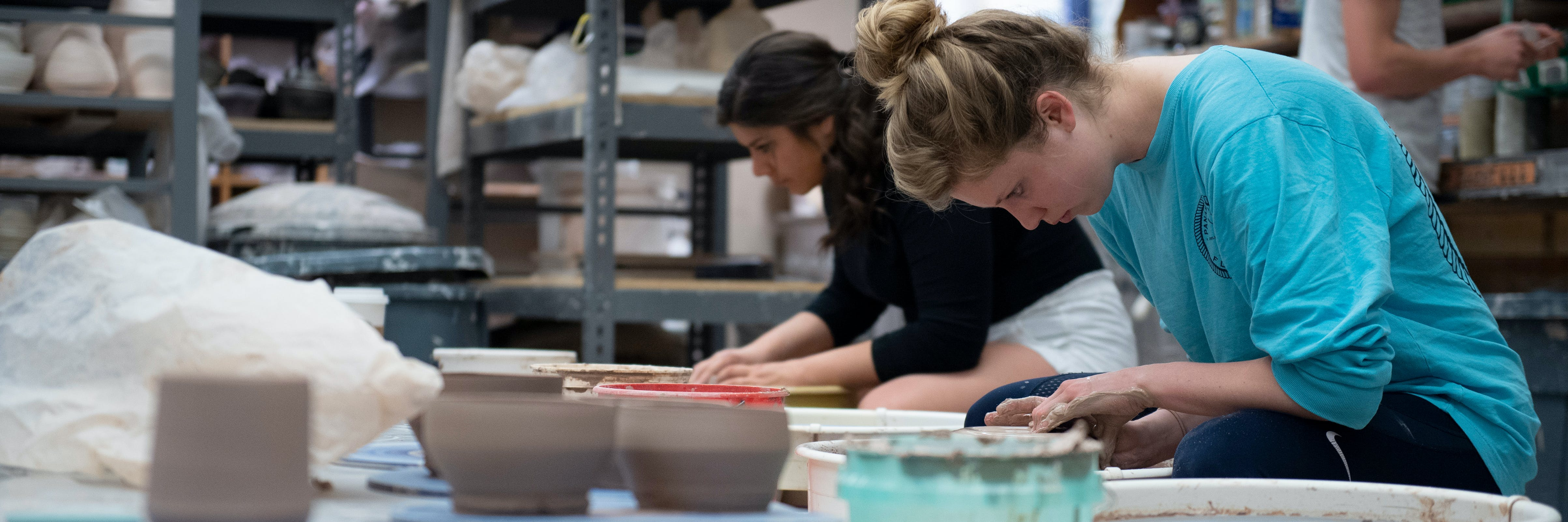 Art students sitting at throwing wheel in ceramics studio