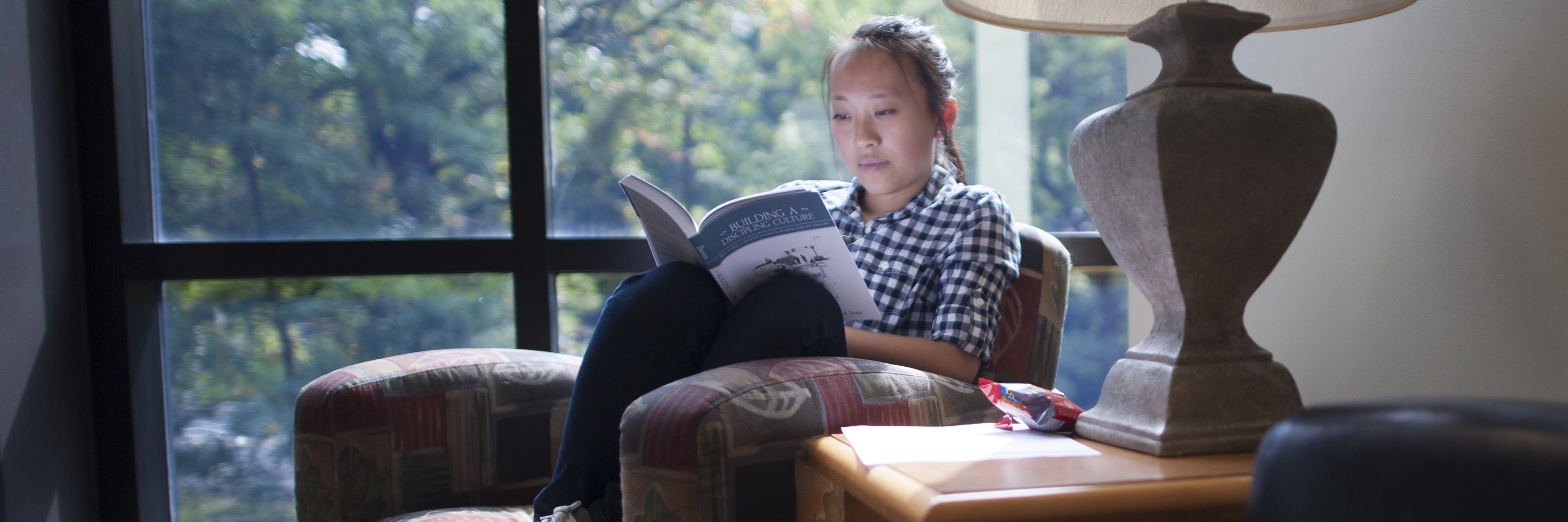 Student reading near a window
