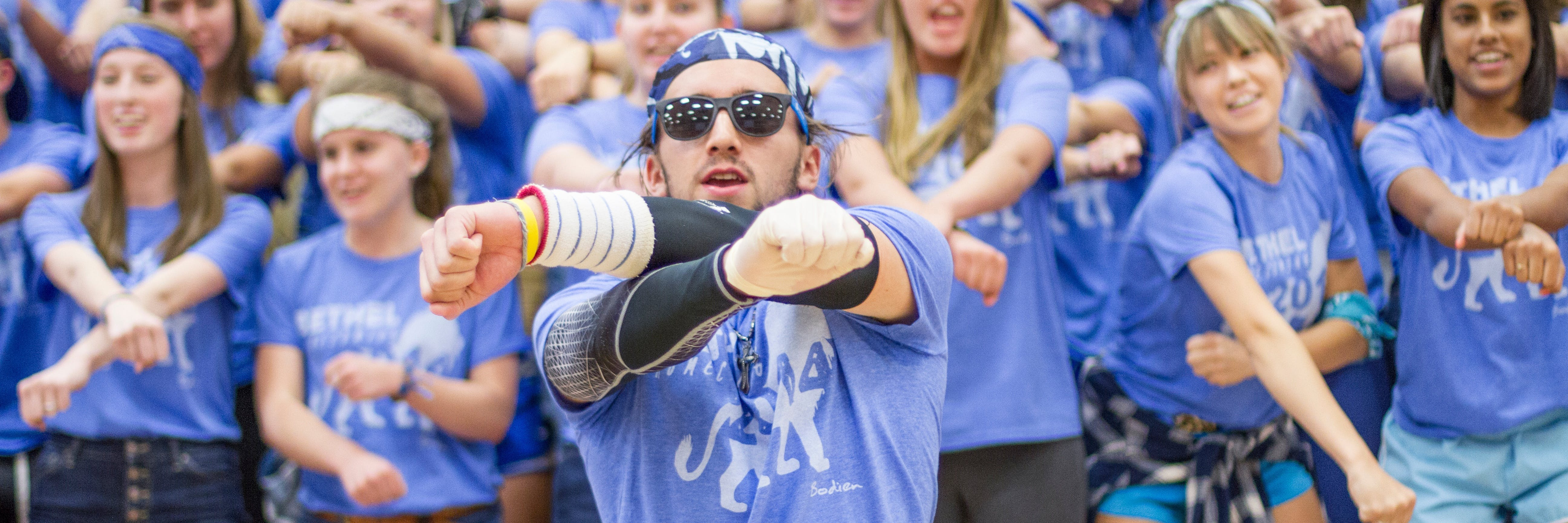 Student leading his residence hall at the homecoming cheer competition