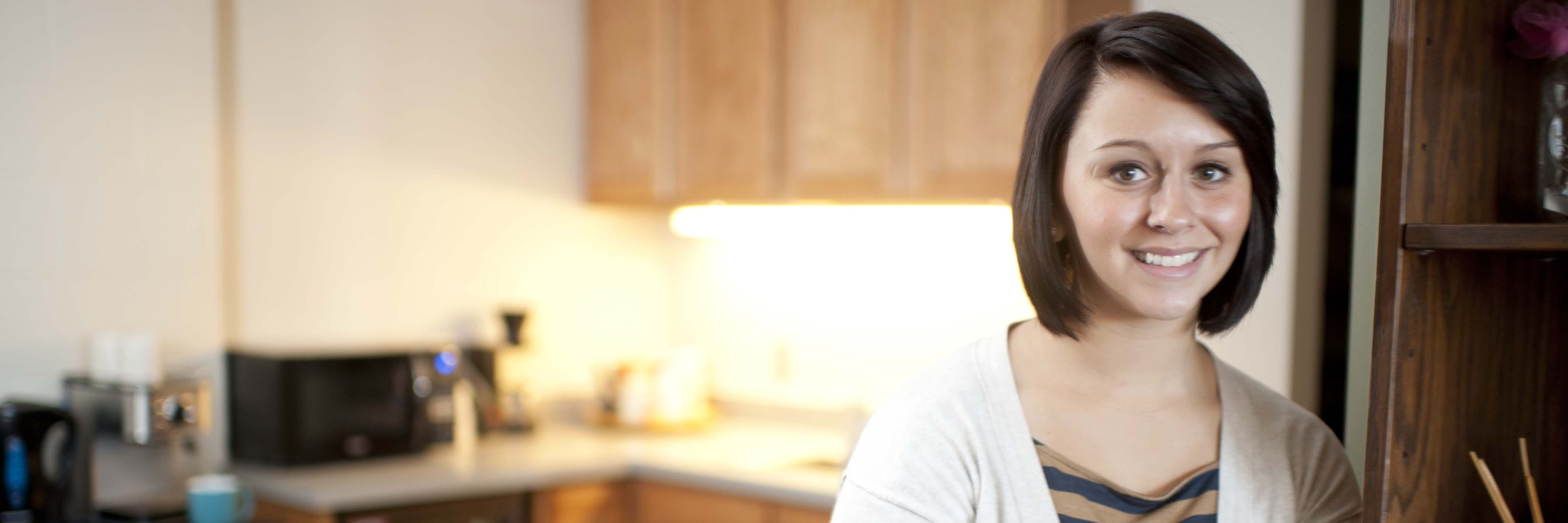 A student stands in a residence hall kitchen.