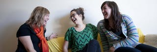 Students laugh together on a couch.